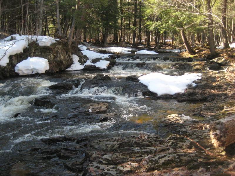 Small upstream drops between snowy rocks