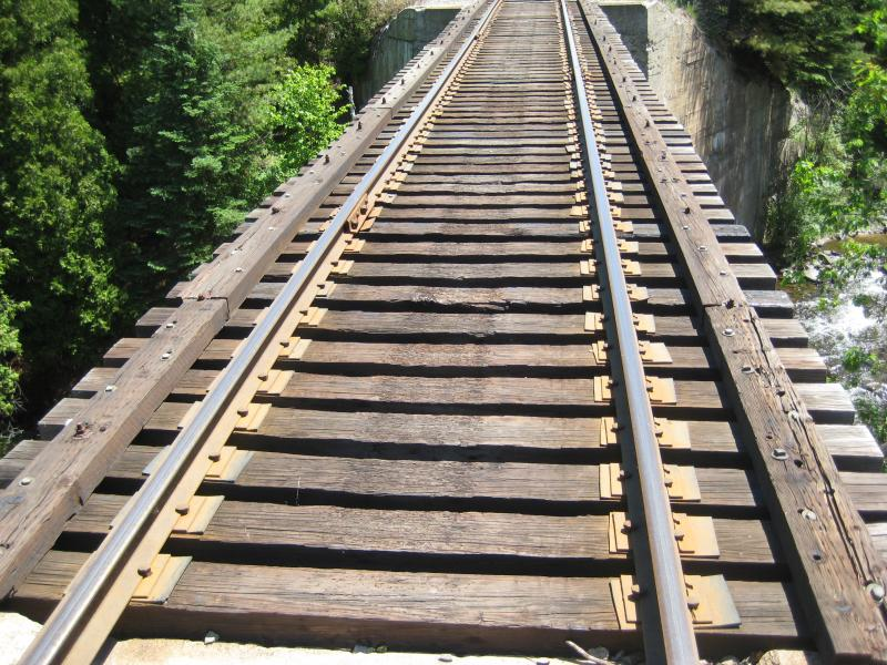 Wooden rail trestle stretching over the river