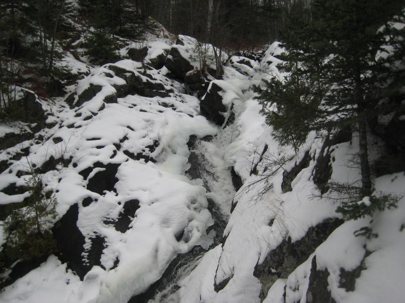 Cascading water surrounded by rock and snow