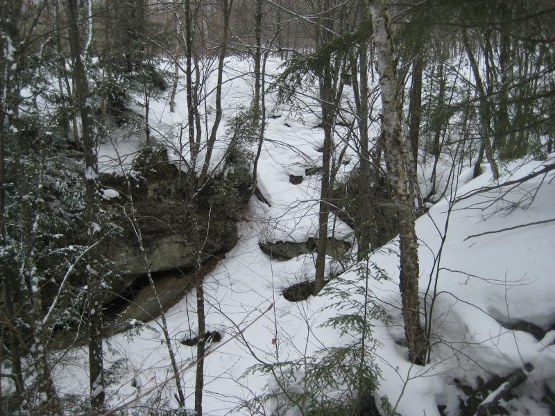 Snow spilling into the creek gorge